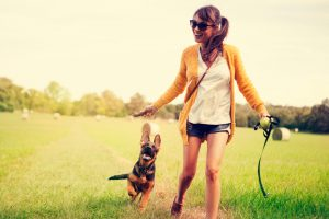 Women enjoy with her dog. They running on field together